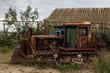 Old rusty broken rural tractor stands in the backyard