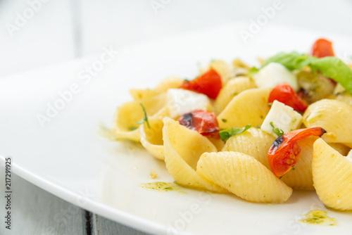 Cuadros en Lienzo Pasta alla caprese, italian pasta with mozzarella, tomatoes and frtesh basil