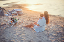 Happy Mother Holding Her Baby Girl On The Beach.