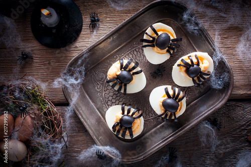 The idea for decorating a table for Halloween: stuffed eggs with spiders from olives, horizontal