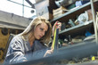 young woman measuring with measuring tape in a workshop