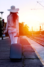 Young Woman With Luggage On Train Station Waiting