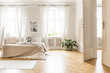 Leinwandbild Motiv Spacious and bright bedroom interior with beige decorations, hardwood floor and a book on the window sill seat
