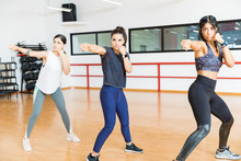 Determined Women Punching The Air In Gym