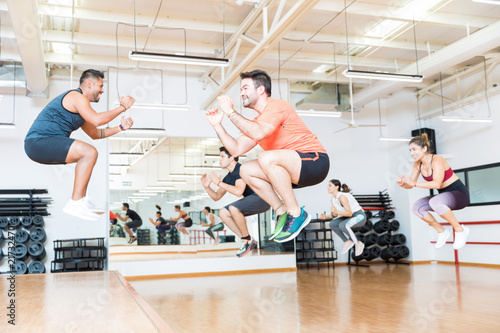 Fotografie, Obraz  Trainer Doing Tuck Jumps With Clients In Health Club