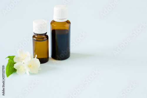 Small brown glass bottles on pastel blue table essential oil with small brown glass bottles on pastel blue table essential oil with jasmine blossoms mightylinksfo