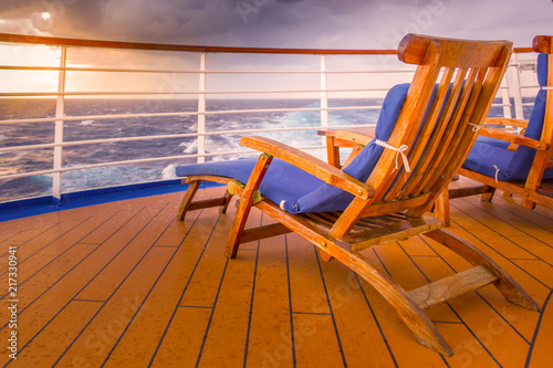 Canvas-taulu Empty chair at sunset on a cruise ship