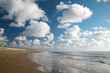 Bank of the blue sea with wet sand and clouds