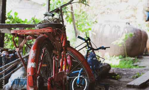 Deurstickers Fiets Old red steel vintage bicycle is parked in very old garage with many other unused stuff such as bamboo, kid bike, used bottle and water tank