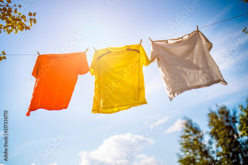 Obraz na plátně  Photo of three T-shirts hanging on rope against blue sky background
