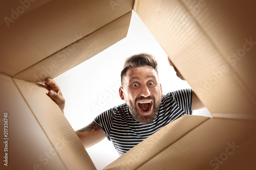 Obraz The surprised man unpacking, opening carton box and looking inside. The package, delivery, surprise, gift lifestyle concept. Human emotions and facial expressions concepts - fototapety do salonu
