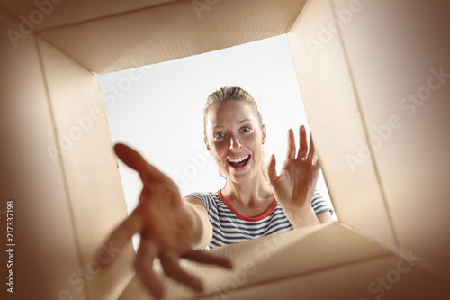 Fotografia, Obraz  The surprised woman unpacking, opening carton box and looking inside
