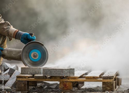 Tablou Canvas grinder worker cuts a stone the electric tool,street construction work
