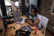 Teenage Blogger Using Laptop At Desk