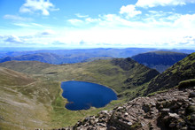 A Lake District Mountain View, From Swirral Edge Over Red Tarn Over To Striding Edge On Helvellyn In The English Lake District On A Summer Day With A Bright Blue Sky