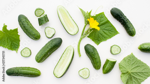 Young cucumbers with cut cucumber and leaf on white Fototapeta