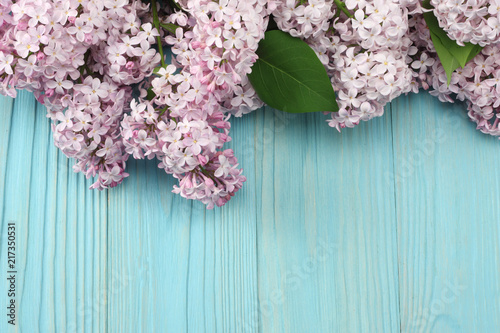 Foto op Plexiglas Lilac pink lilac flower on blue wooden background. top view with copy space