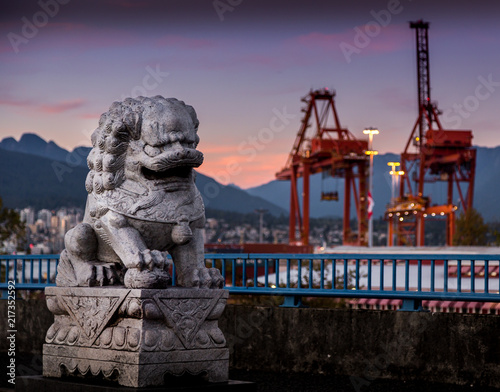 Fotografia  Stone lion statue near the port of Vancouver at sunset.