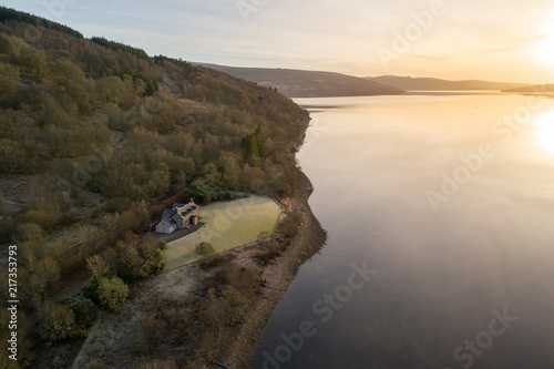 Sunset View of Secluded House Next to a Loch in Scotland Wallpaper Mural