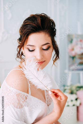 Fotobehang Akt Sensual brunette in silk white robe waiting on the bed