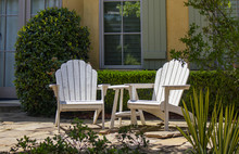 Two White Adirondack Chairs Sitting On A Patio In Front Of Windows With Green Shutters And A Hedge With Plants Around Them
