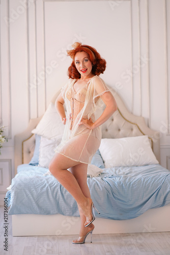 96ce85d9a charming vintage girl posing in beige pin-up lingerie and tight corset with sheer  nightgown on top