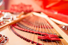 Strings Inside A Red Grand Piano. Piano Playing, Dampers, Felt Hammers, Bronze Strings And Metal Frame.