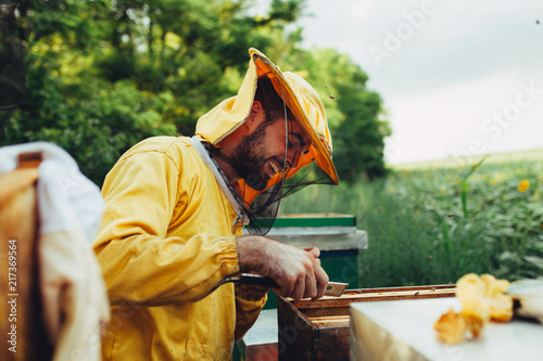 Happy beekeeper working in his apiary Canvas Print