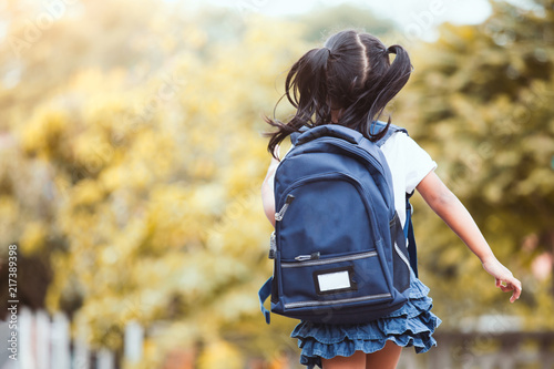 Obraz Back to school. Cute asian child girl with backpack running and going to school with fun - fototapety do salonu
