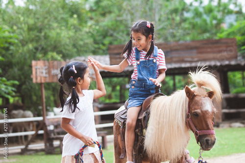 Cute asian child girl riding a pony and making hi five gesture with her elder si Canvas Print