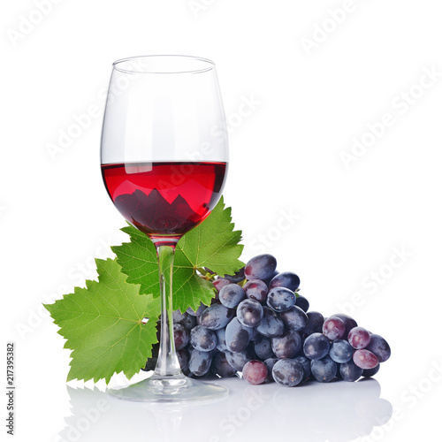 Glass with red wine for tasting with fresh grape and green leaf Fototapete