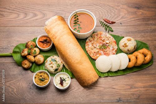 Fototapeta Group of South Indian food like Masala Dosa, Uttapam, Idli/idly, Wada/vada, sambar, appam, semolina halwa, upma served over banana leaf with colourful chutneys, selective focus obraz