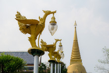 Bronze Casting Thai Literature Swans Carrying Bell-shaped Electricity Lantern Painted With Gold Colour Located In The Temple's Garden With Finial Of Wat Pha Phu Gon Buddhism Pagoda In The Background