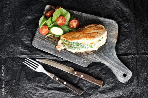 Fototapeta Chicken breast stuffed with spinach and ricotta. Chicken breast on a wooden board. Next to fresh vegetables. In the frame cutlery. Dark background. View from above. Close-up. obraz