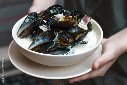 Mussels with onions and bacon in cream sauce in deep plate in woman hands