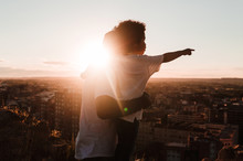 Father And Son In A Cliff Observing The City In A Sunset Of Summer, Builds Background