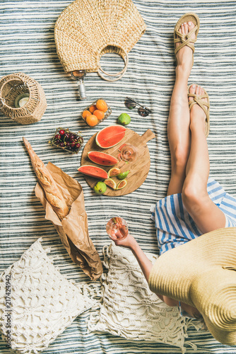 Keuken foto achterwand Summer picnic setting. Young woman in striped dress and straw sunhat sitting with glass of rose wine in hand, fresh fruit on board and baguette on blanket, top view. Outdoor gathering or lunch concept