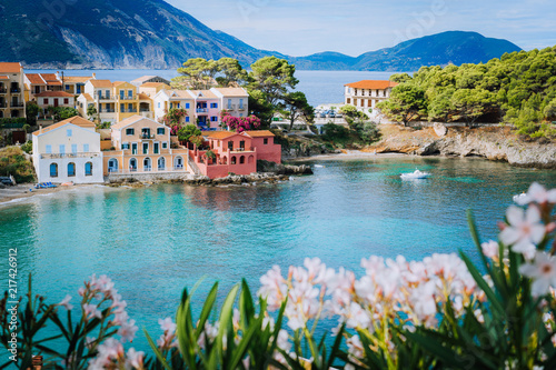 Recess Fitting Nice Bright white flower blossom in front of turquoise colored bay in Mediterranean sea and beautiful colorful houses in Assos village in Kefalonia, Greece