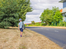 Day View Little Child Boy Traveller With Backpack Walking Along UK Road