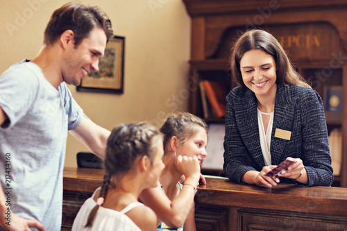 Happy family checking in hotel at reception desk Poster Mural XXL