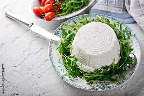 Fototapeta Ricotta cheese with arugula and tomatoes on plaster background obraz