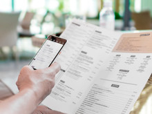 Person's Hands Holding Menu And Mobile Phone In Restaurant. A Foreign Man In Cafe Ordering Food Using Word Translation Program While Sitting At Table. Mockup For Smartphone Screen