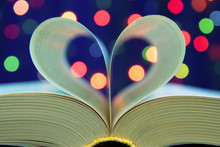 Open Book With Heart Shape From Paper Pages On Table In Soft Night Light Holiday Style Close Up With Bokeh Blur Background . For Christmas And Valentine's Day