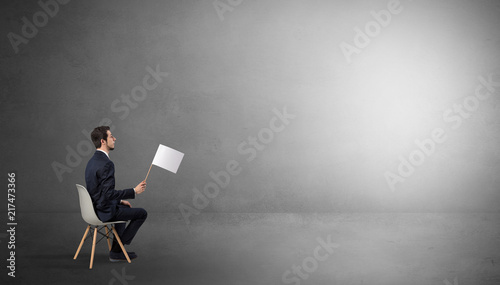Businessman staying in an empty grey dark room with stuffs on his lap Wallpaper Mural