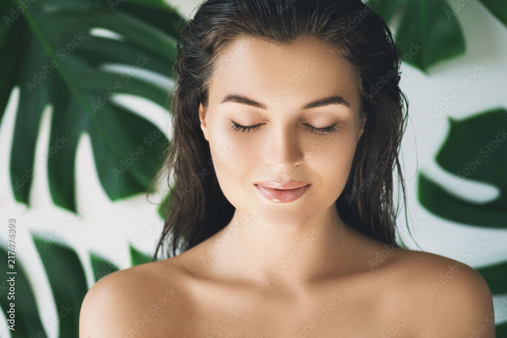 Fototapety, obrazy: Portrait of young and beautiful woman with perfect smooth skin in tropical leaves