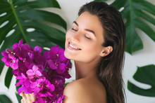 Young And Beautiful Woman With Perfect Smooth Skin Is Holding Orchid Flowers
