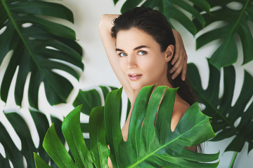 Fototapeta Do salonu kosmetycznego Portrait of young and beautiful woman with perfect smooth skin in tropical leaves