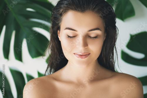 Portrait of young and beautiful woman with perfect smooth skin in tropical leaves - fototapety na wymiar