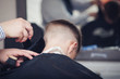 Back view of cute boy getting hairstyle by hairdresser in barbershop.