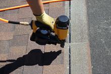 Roofer Builder Worker With Nailgun Installing Asphalt Shingles Or Bitumen Tiles On A Roof Of A New House.